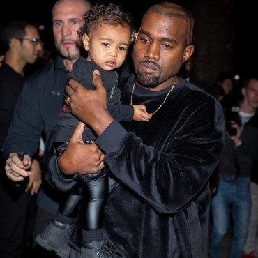 North West et Kanye West pour le défilé Balenciaga à Paris lors de la Fashion Week parisienne le 24 septembre 2014